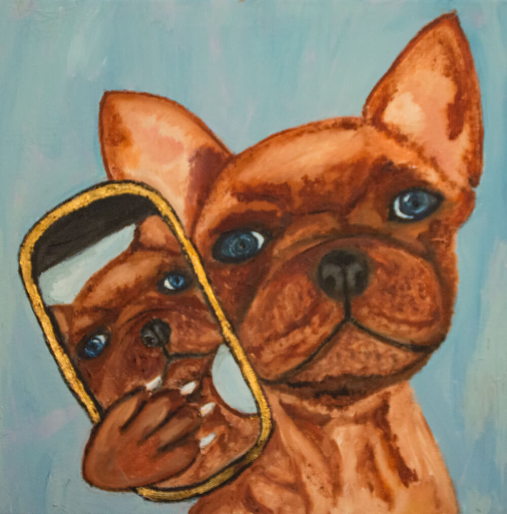 A dog holding a selfie he made of himself on a phone